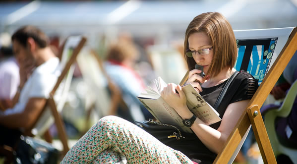 Woman in a deckchair reading a book outside