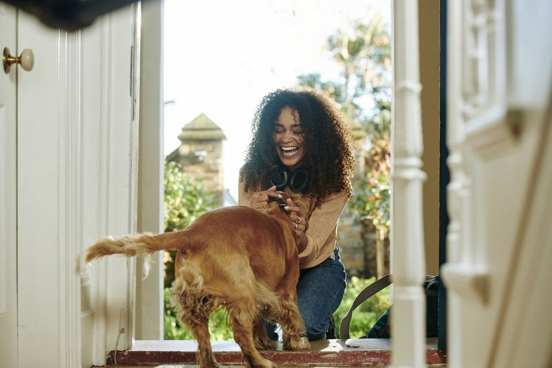 Woman excitedly greets her dog in the hallway