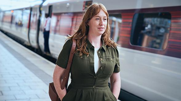 Woman walking down train station platform next to an LNER Azuma