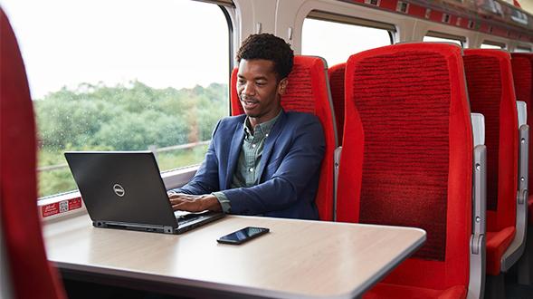Man sat on train working on laptop