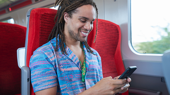 Man sat on a train using a mobile phone